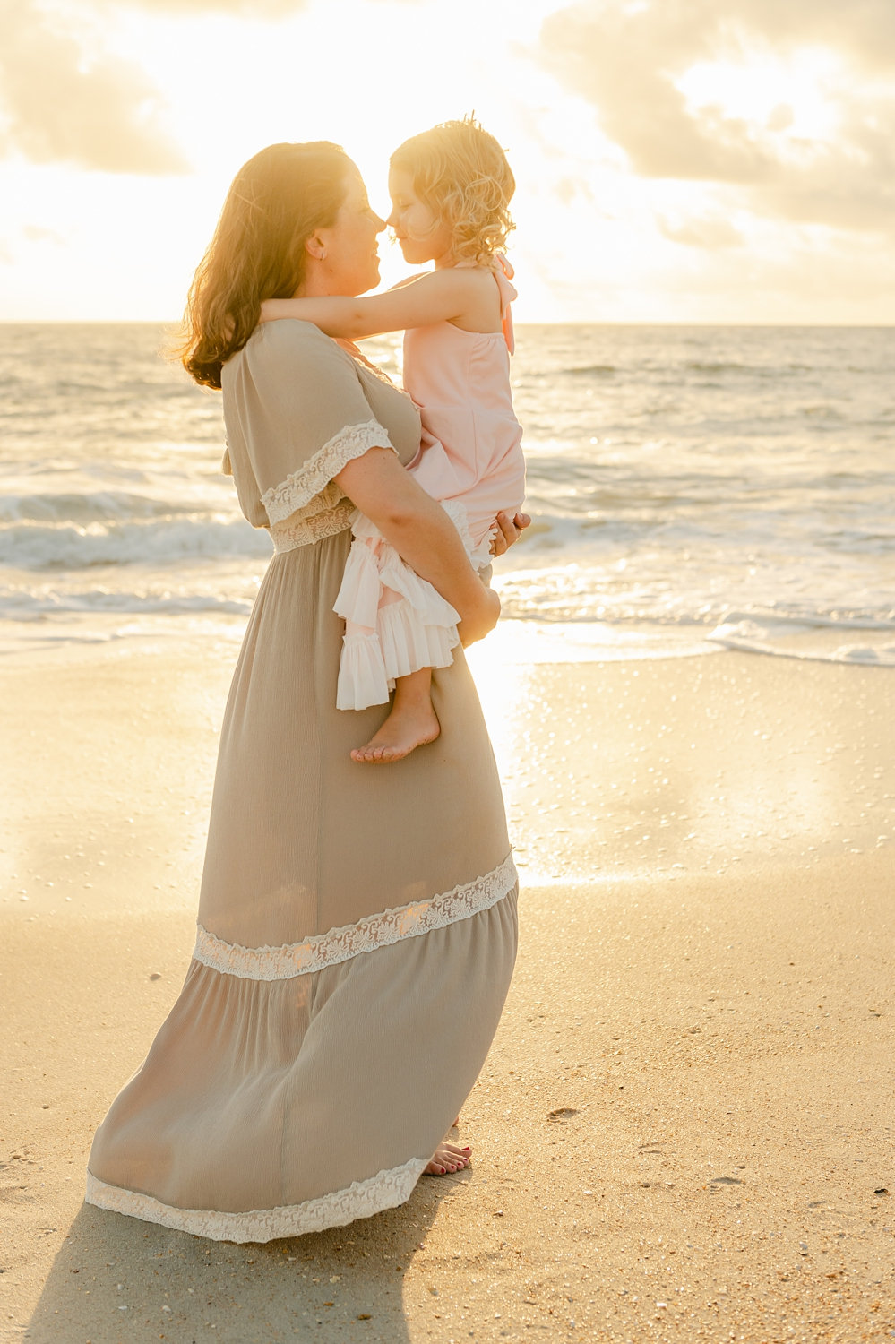 mom and daughter touching noses with the sun rising over the Atlantic ocean behind them