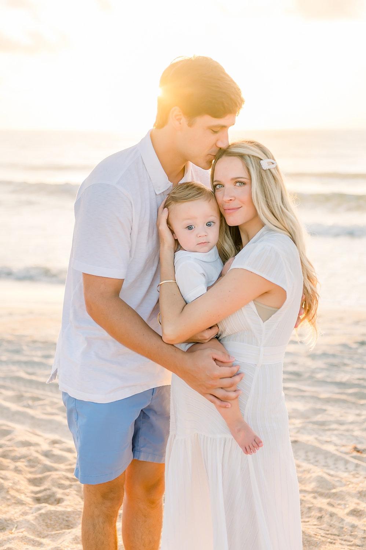 husband kissing wife's forehead, family of three, Florida family coastal portrait session