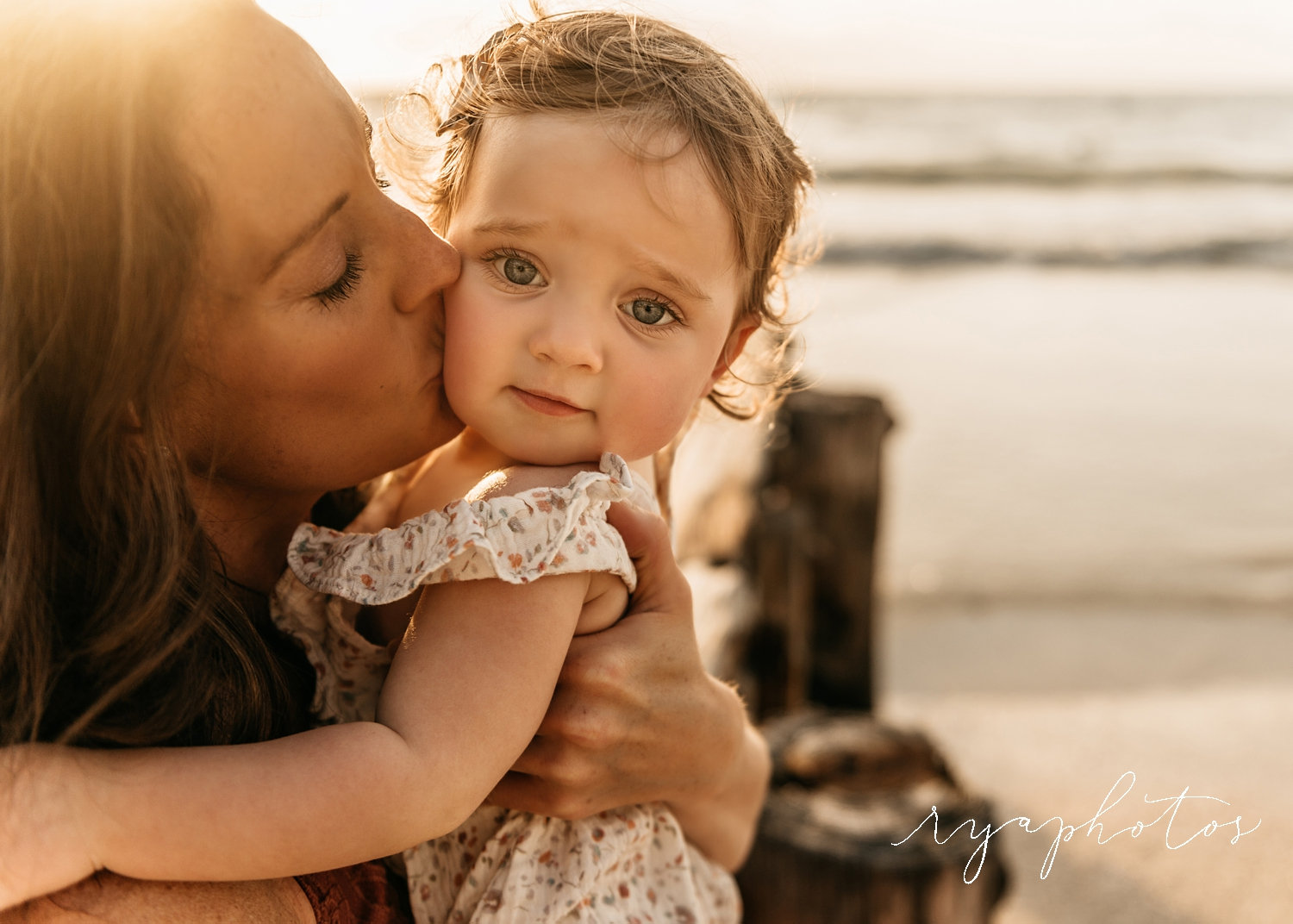 mother kissing baby daughter, baby girl with big blue eyes, sun flare, Rya Duncklee