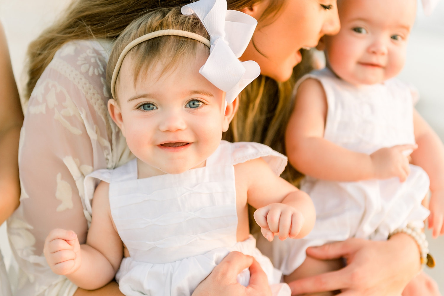 adorable twin girls in the arms of their mom, golden hour sunrise photography