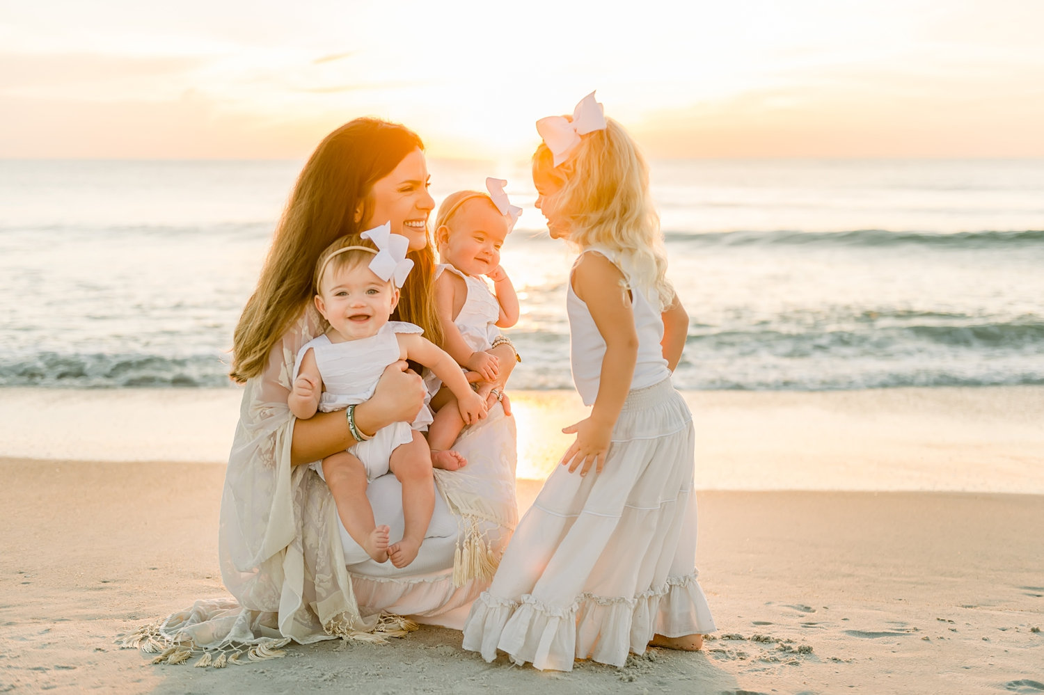 mother holding twin girls, little girl looking at her mom and sisters, sunrise